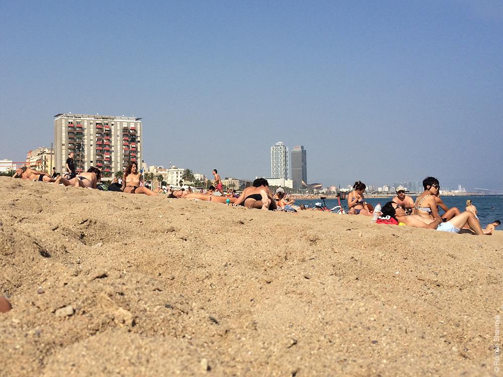 Нудисты загараются на пляже в Барселоне