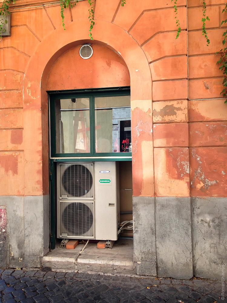 Кондиционер на фасаде в Риме. Кондиционер в окне здания в Риме
